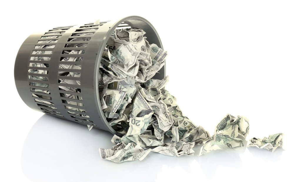 Money dumped in a tipped over trash bin to symbolize the money wasted on expensive leaf blowers.