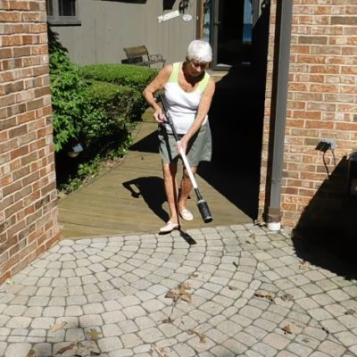 A lady is cleaning her walkway with the lightweight and cordless ZoomBroom.